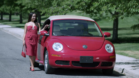Slow motion of woman in red dress walking and posing next to red volkswagon bug Footage