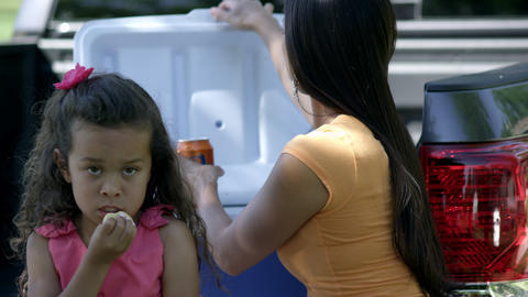 Up close view of mother handing cookie to daughter then drinking a soda Footage