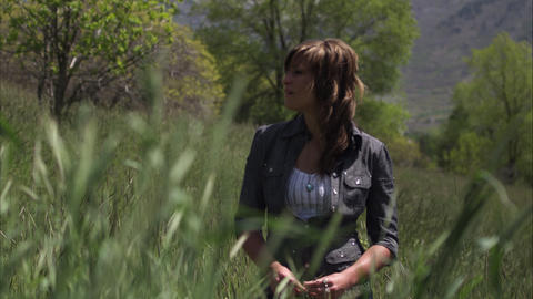 Slow motion shot of a young woman standing in tall grass Footage