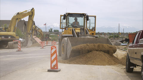 Static shot of a bulldozer picking up a load of dirt Footage