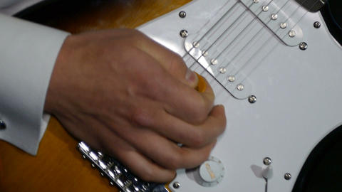 The musician is actively playing the guitar in the recording studio close-up Live Action