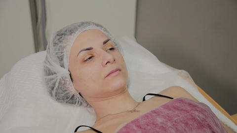 Beautiful young woman in bathrobe lying and waiting facial care procedure at Footage