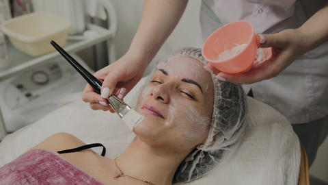 Skilled cosmetologist puts mask on face of lying woman in... Stock Video Footage