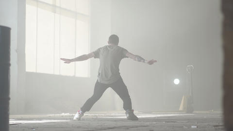Great young hip-hop dancer performing in the fog. Hip hop culture. Rehearsal Live Action