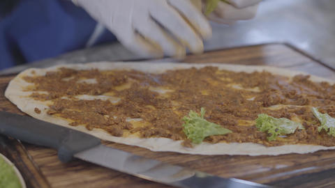 Hands of man in rubber gloves preparing dish wrapped in lavash. Chef hand Footage
