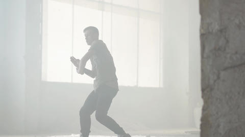 Young hip-hop dancer performing in the fog. Hip hop culture. Rehearsal Live Action