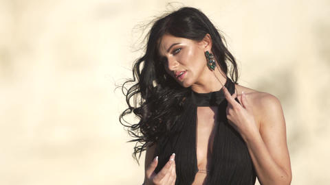Young woman in black evening dress at backdrop of cliff Wind blow her black hair Footage