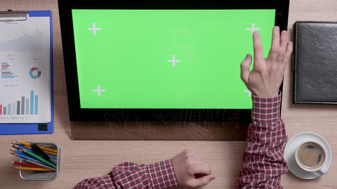 Top view of a man's hands touch the top right corner of a green screen on touch Live Action