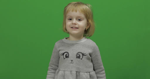 Kid girl on a Green Screen, Chroma Key. Happy three years old girl Footage
