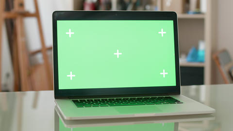 Parallax shot of a laptop with green screen on and people on the background Footage