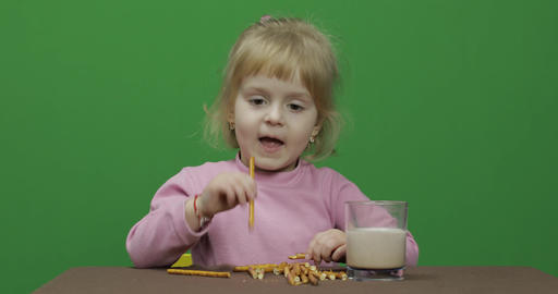 The child eats cookies. A little girl is eating cookies sitting on the table Live Action