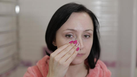Beautiful brunette woman using cotton pads. Woman removing makeup Footage