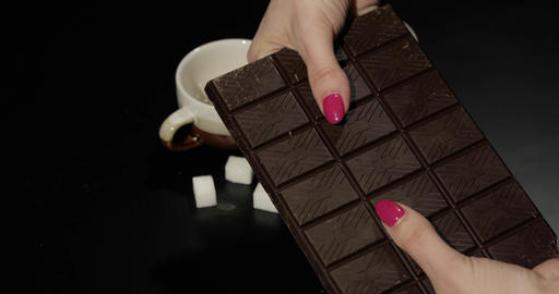 Woman breaks black chocolate bar. Close-up shot of woman fingers Footage
