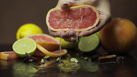Woman squeezing a fresh and juicy grapefruit with hands. Fresh fruits Live Action