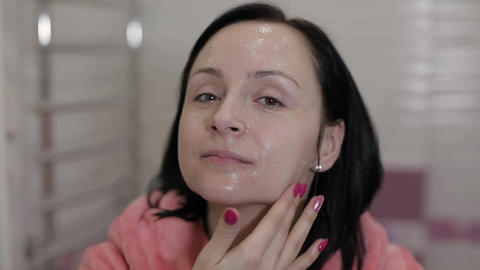 Young Caucasian Woman Applying Cream Mask on Face. Facial Spa Procedure at Home Footage