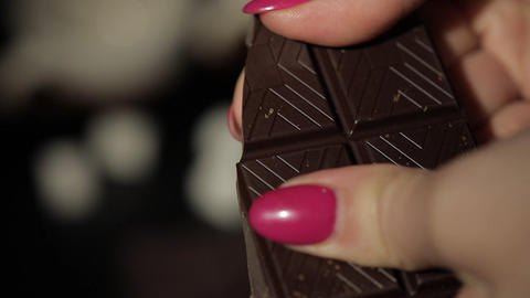 Woman breaks black chocolate bar. Close-up. Slow motion Footage
