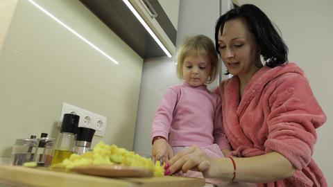 Cute small girl cooking with her mother. Little daughter with mother together Live Action
