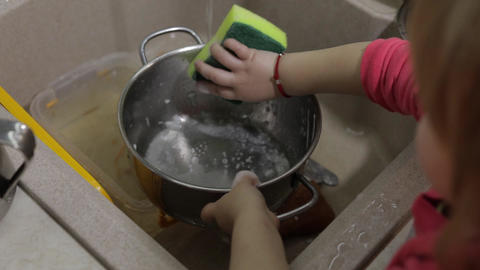 Child washing dishes in the kitchen. Close up of girls hands Live Action