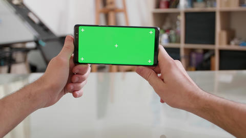 Mans point of view holding a smartphone horizontally with green screen on Live Action