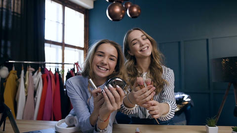 Close up portrait of two handsome women holding make up tools in the hands and Live Action