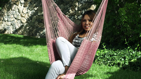 Tilting handheld shot of an Asian woman on a hammock Footage