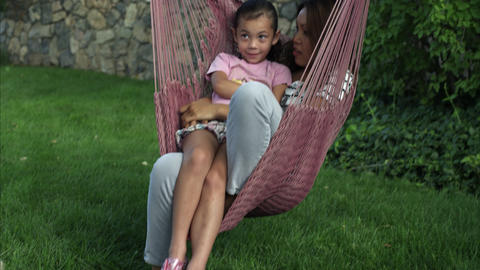Handheld shot of a young woman sitting in a hammock talking to a little girl Footage