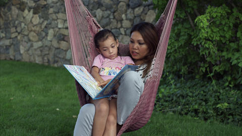 Tilting shot of Asian woman and child reading a book on a hammock Footage