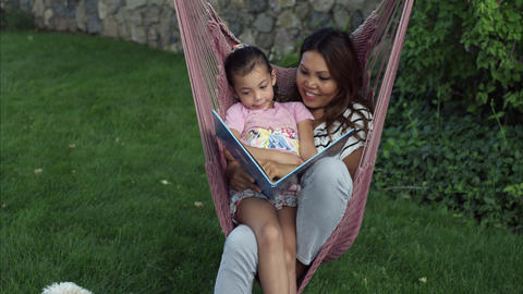 Tilt shot of Asian woman and child reading a book on a hammock Footage