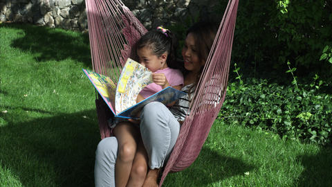 Handheld shot of an Asian mom and daughter reading a book on a hammock Live Action