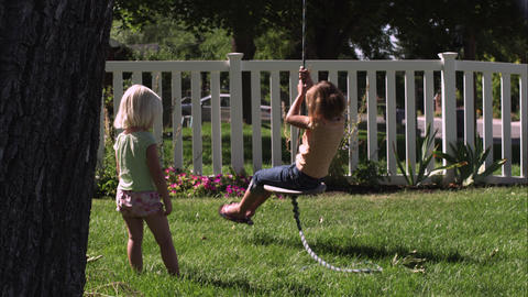 Slow motion handheld shot of a child swinging on a tree swing while another one  Footage