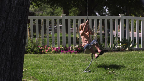 Slow motion handheld shot of a child riding a tree swing Live Action