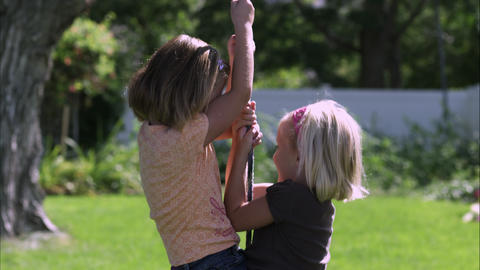 Slow motion handheld shot of two girls sharing a tree swing Live Action