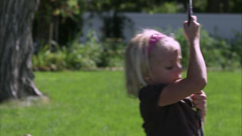 Tilt shot of a little girl playing on a tree swing in slow motion Footage
