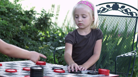Slow pan of two little girls playing checkers Live Action