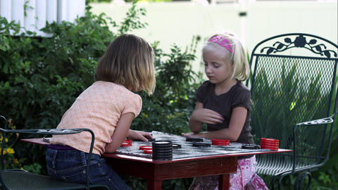 Handheld shot of two little girls playing checkers in slow motion Footage