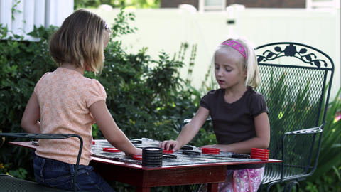 Slow static shot of two little girls playing checkers Live Action