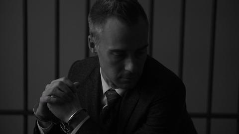 A cuffed white collar criminal in prison (B/W Version) Footage