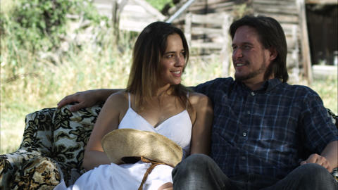 Dolly shot of a smiling couple sitting on a couch in the middle of a clearing Footage