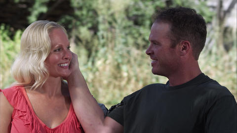 Slow tracking shot of a couple smiling and touching while outdoors at a farm Footage