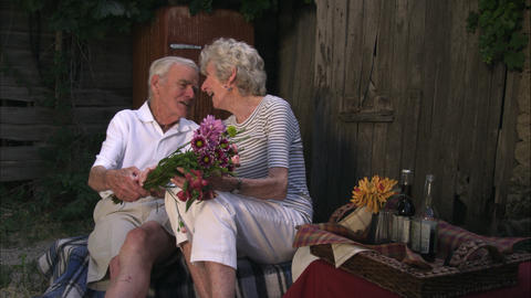 Slow static shot of an old man surprising an elderly woman with a bouquet of flo Footage