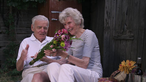 Slow static shot of an elderly man surprising his wife with a bouquet of flowers Footage