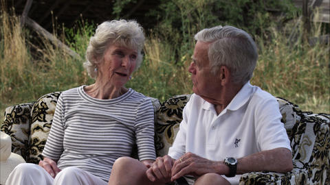 Slow static shot of old couple talking while sitting on a couch outdoors Footage