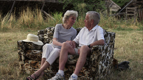Slow tracking shot of an affectionate elderly couple having a conversation outdo Footage