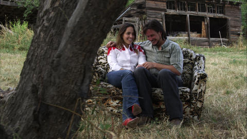 Slow dolly shot of an affectionate young couple talking on a couch outdoors at a Footage