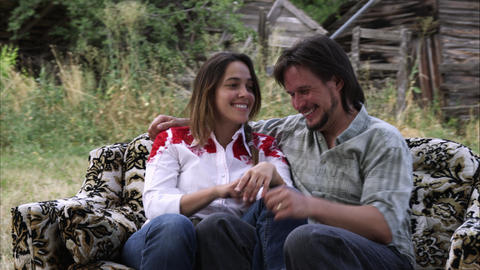 Slow tracking shot of a sweet young couple on a couch outdoors at a farm Footage