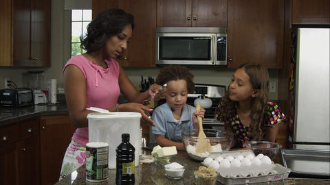Slow motion of mother, boy, and girl mixing ingredients Footage