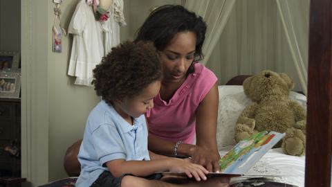 Slow motion of mother reading book to young boy Live Action
