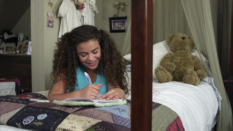 Slow motion pan of girl nodding and writing in diary Footage