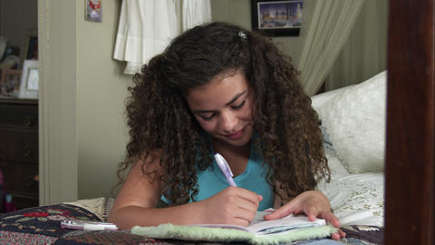Slow motion pan of girl writing in diary Footage