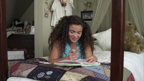 Slow motion pan of girl smiling while writing in her diary Footage